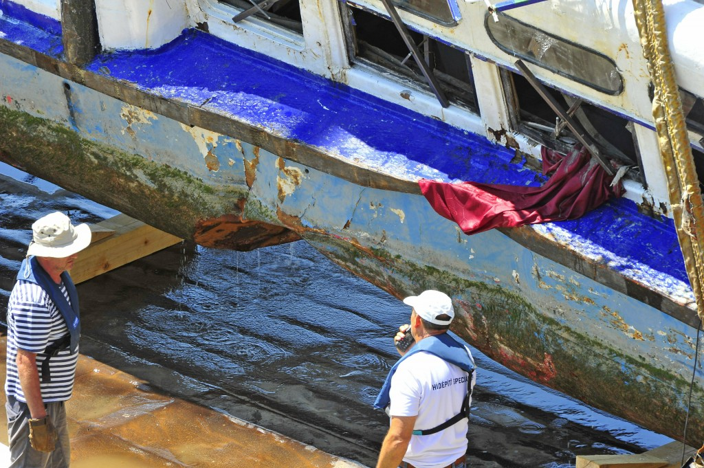 People stand next to the wreckage of the sightseeing boat on a transporting barge at Margaret Bridge, the scene of the fatal boat accident in Budapest...