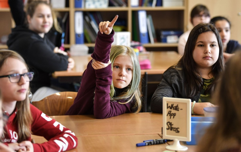 Pupil Vanessa Weyer, center, raises her hand during a lesson in social media and internet at a comprehensive school in Essen, Germany, Monday, March 1...