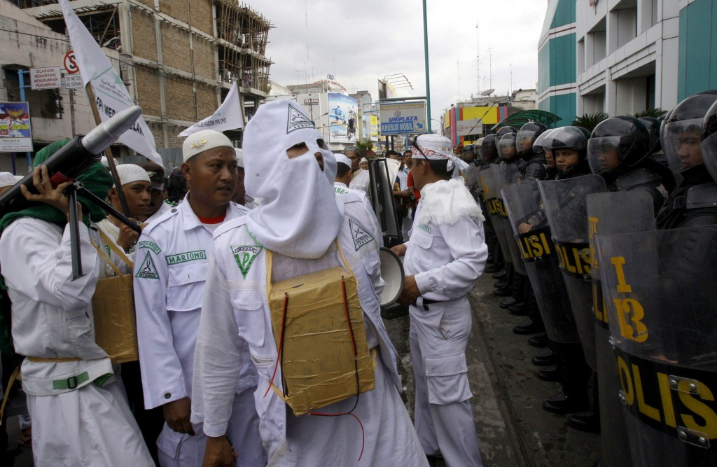FILE - In this Nov. 23, 2012, file photo, a Muslim protester of Islam Defenders Front (FPI) wears a mock-suicide bomb during a demonstration against I