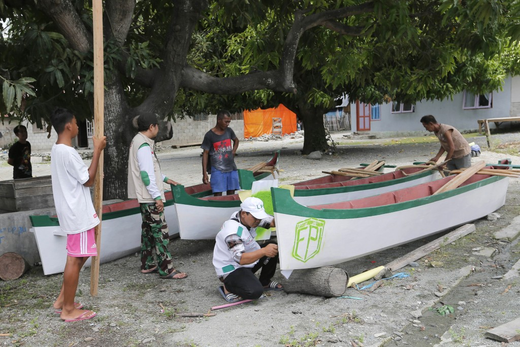 In this April 2, 2019, photo, members, center, of Islamic Defenders Front help local fishermen to build boats at a fishing village affected by the 201