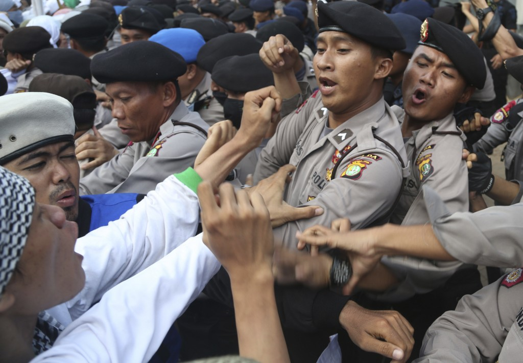 FILE - In this Nov. 22, 2013, file photo, Indonesian police officers block members of the militant Islamic Defenders Front (FPI) during a demonstratio