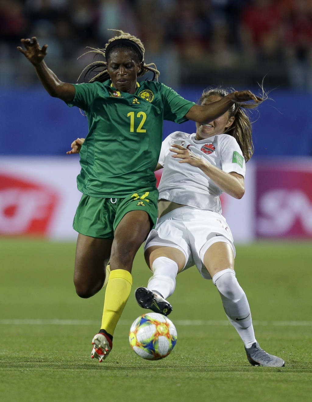 Cameroon's Claudine Meffometou, left, and Canada's Janine Beckie battle for the ball during the Women's World Cup Group E soccer match between Canada