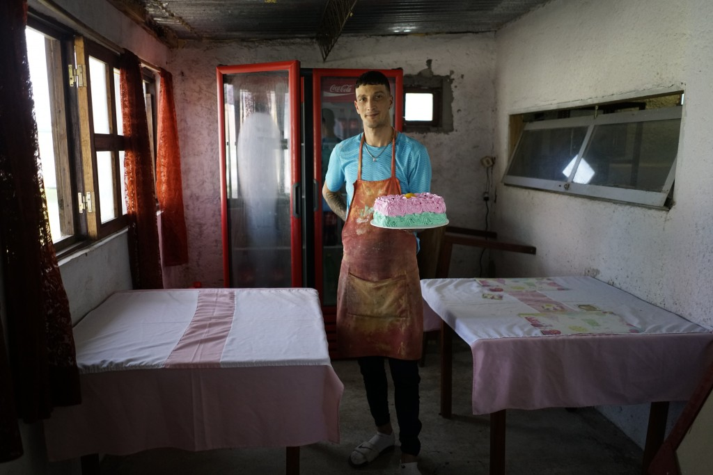 In this May 18, 2019 photo, inmate Nelson Avantti, who runs a bakery inside the Punta de Rieles prison, holds a cake at his bakery at the prison in Mo...