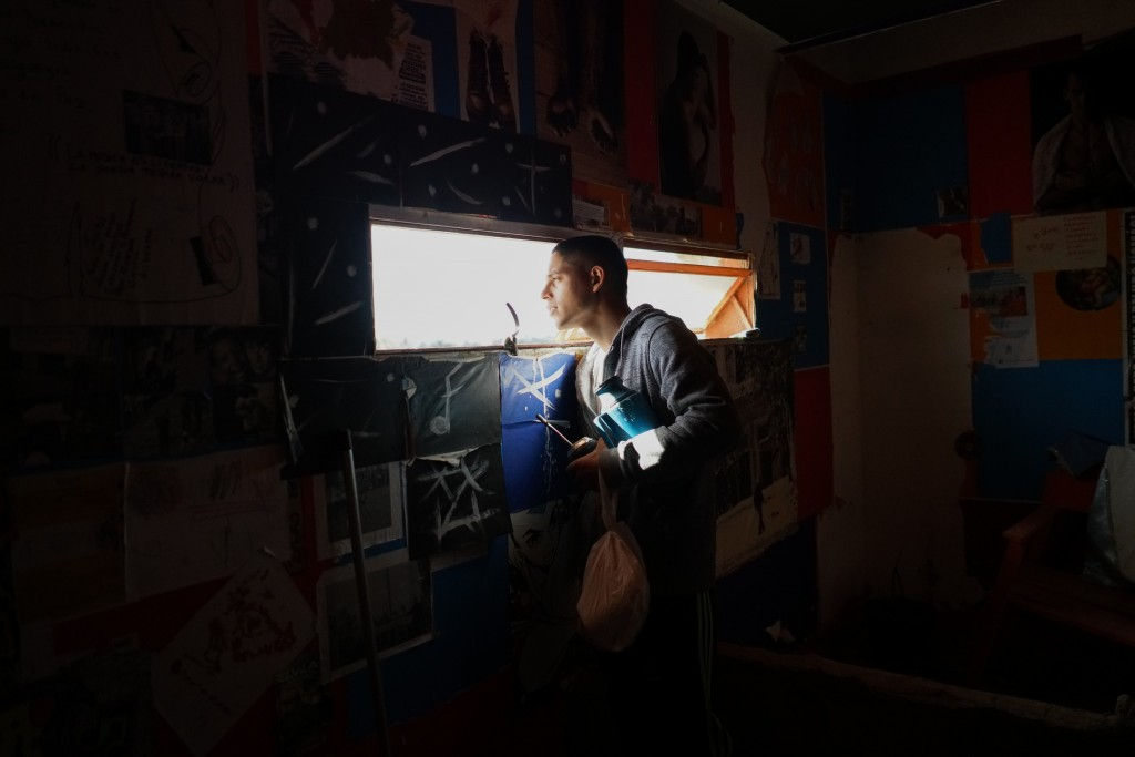 In this May 15, 2019 photo, an inmate looks through the window of the Punta de Rieles prison in Montevideo, Uruguay. Uruguay has 11,000 inmates in cro...