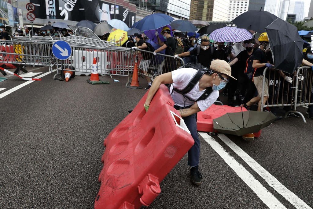 In this June 12, 2019, file photo, a protester moves a barricade to build a makeshift blockade near the Legislative Council in Hong Kong. (AP Photo/Vi