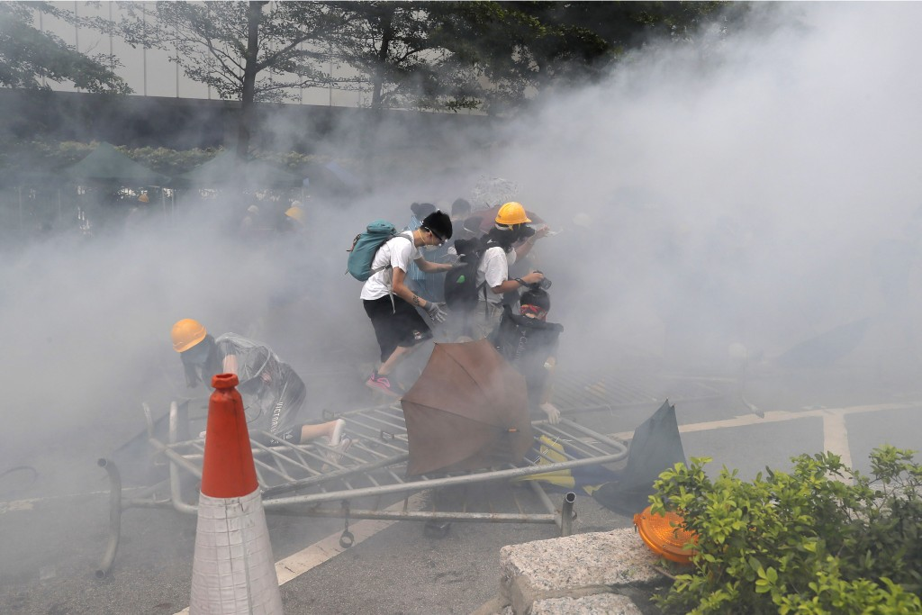 In this June 12, 2019, file photo, protesters react to a cloud of tear gas near the Legislative Council in Hong Kong. (AP Photo/Kin Cheung, File)