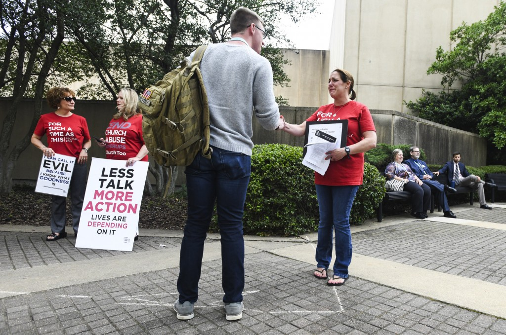 Jules Woodson, right, of Colorado Springs, Colo., hands out flyers while demonstrating outside the Southern Baptist Convention's annual meeting Tuesda