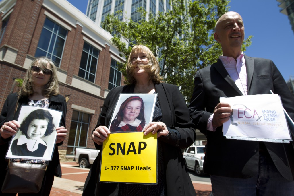Becky Ianni, center, a victim of priest abuse, holds a picture of her younger self along with other demonstrators outside the venue where the United S...