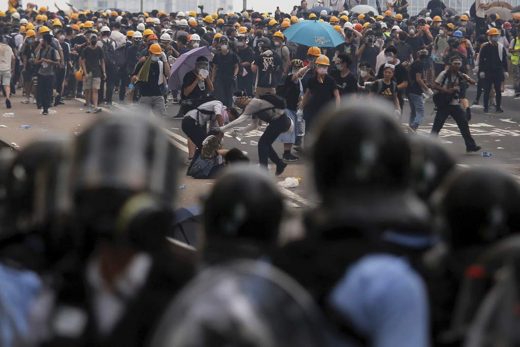 Protesters help a fallen person after clashing with riot police during a massive demonstration outside the Legislative Council in Hong Kong, Wednesday