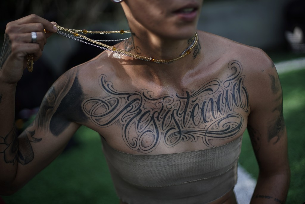 """In this May 13, 2019 photo, transgender Caua Fraga, 23, shows the tattoo on his chest that reads in Portuguese """"Resistance"""", before a training session..."""