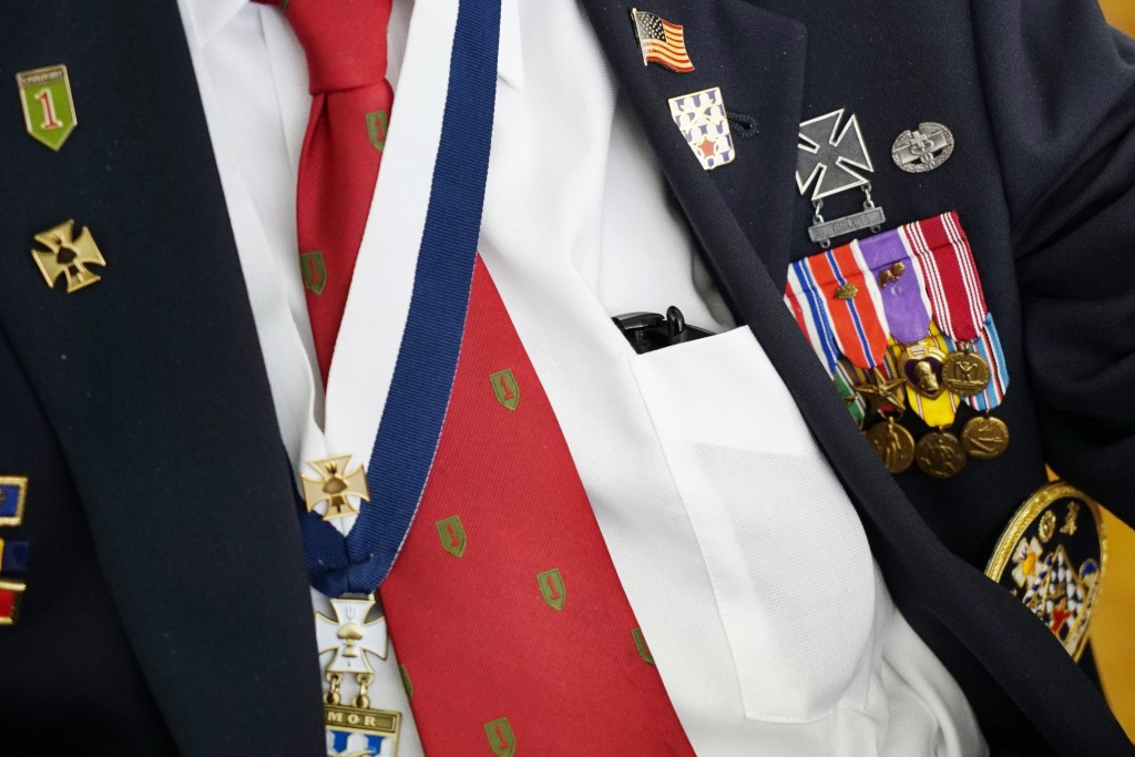 A row of medals, including four Purple Hearts and three Silver Stars, are worn by D-Day survivor Ray Lambert during a reception at the American Milita