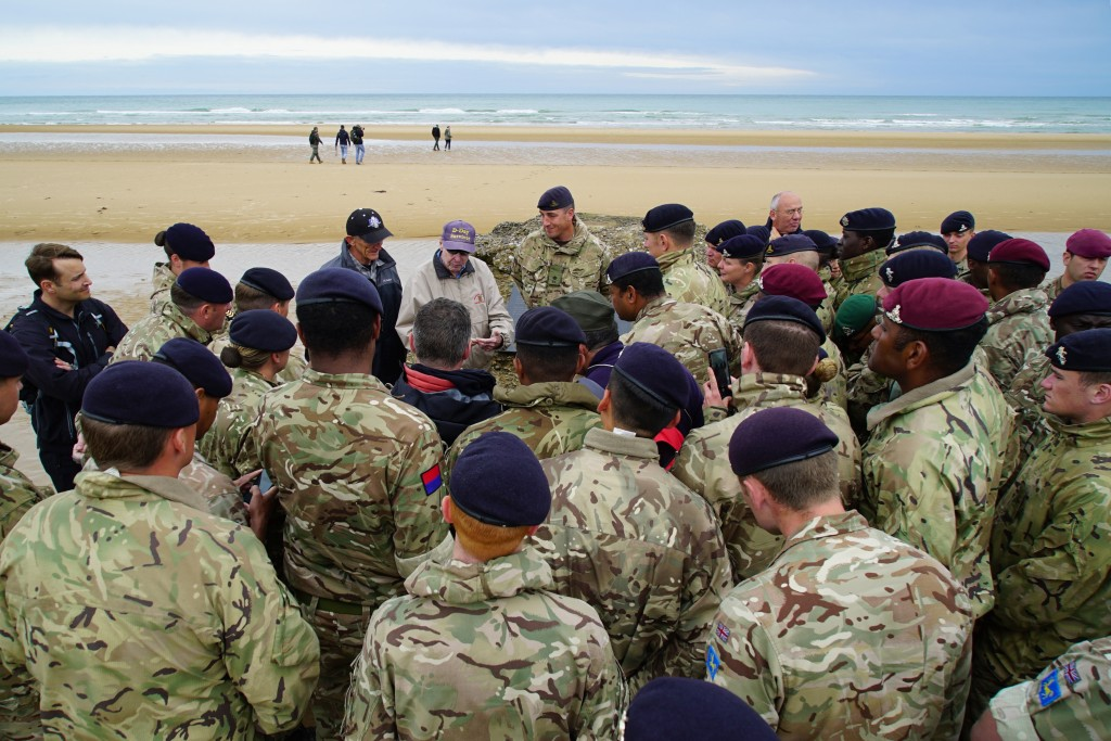 Members of the 12th Regiment, Royal Artillery, gather around to listen in as D-Day survivor Ray Lambert shares war stories on Omaha Beach in Collevill