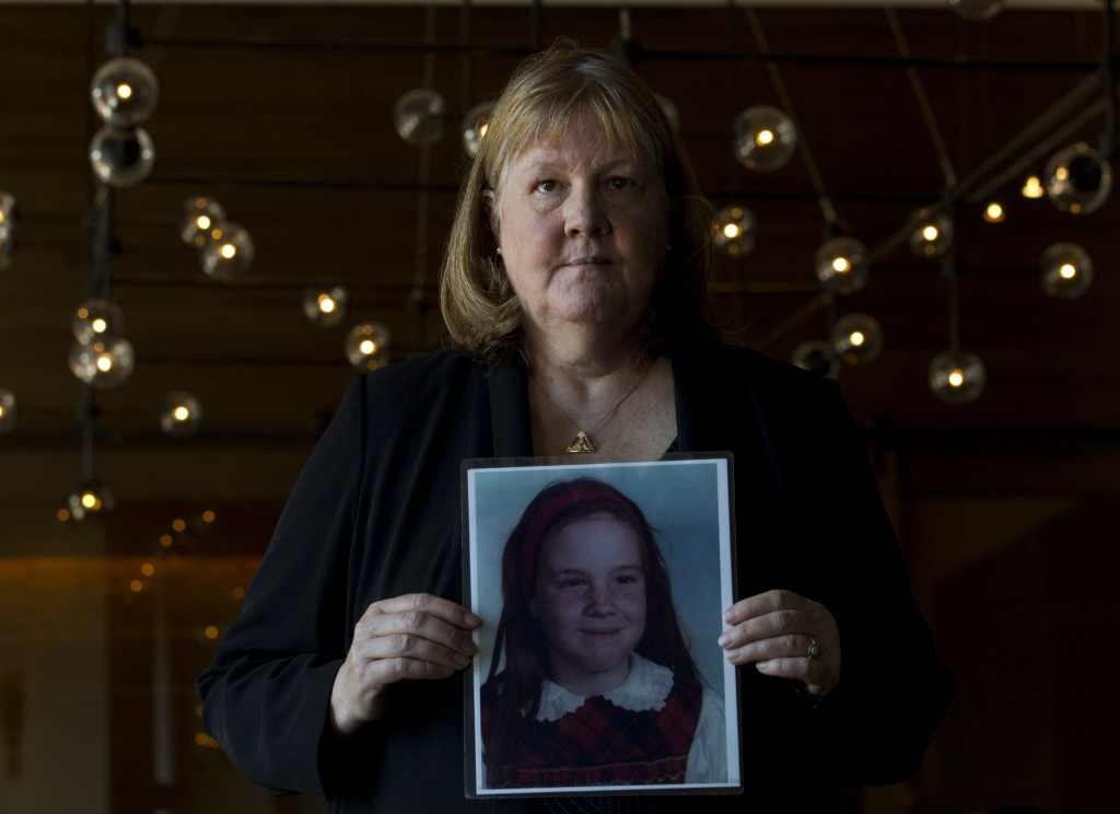 Becky Ianni, a victim of priest abuse, poses for a portrait with a picture of her younger self, during the United States Conference of Catholic Bishop...