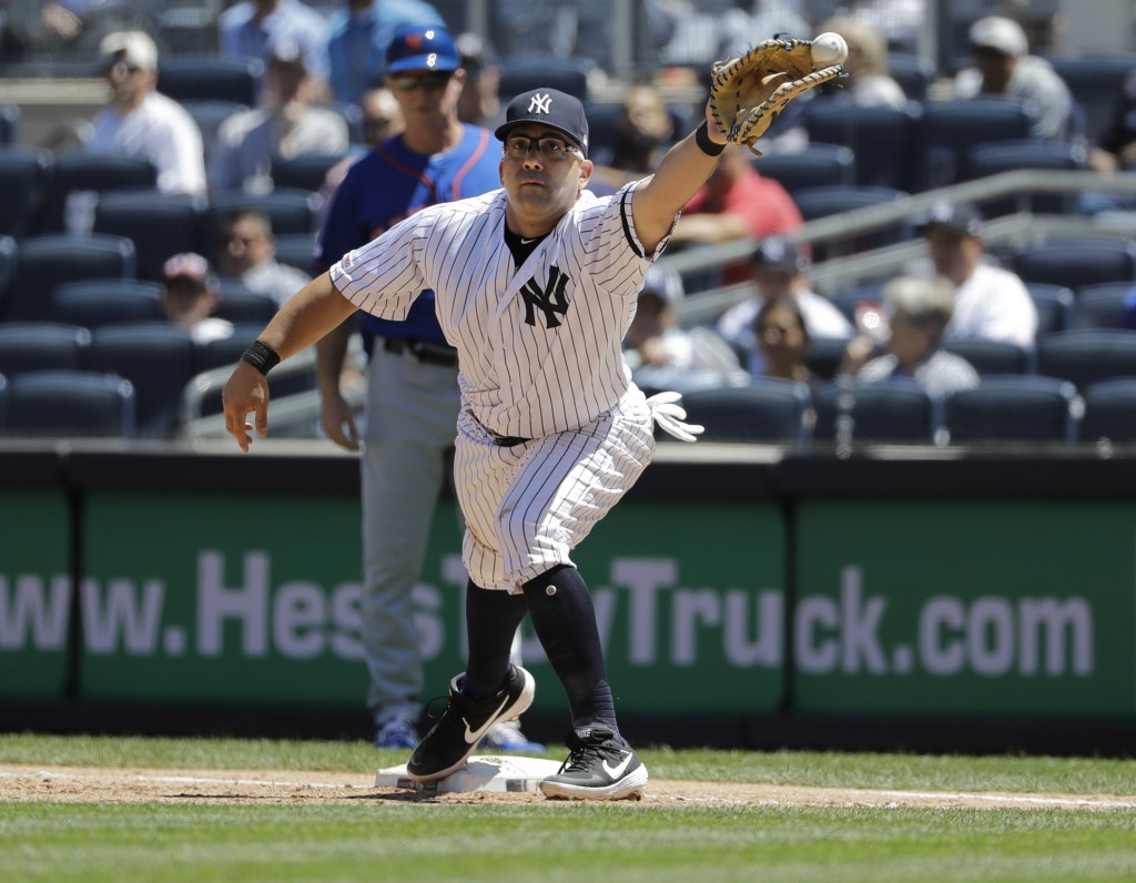 New York Yankees first baseman Kendrys Morales can't field the throw allowing New York Mets' Todd Frazier to reach first base during the fourth inning...