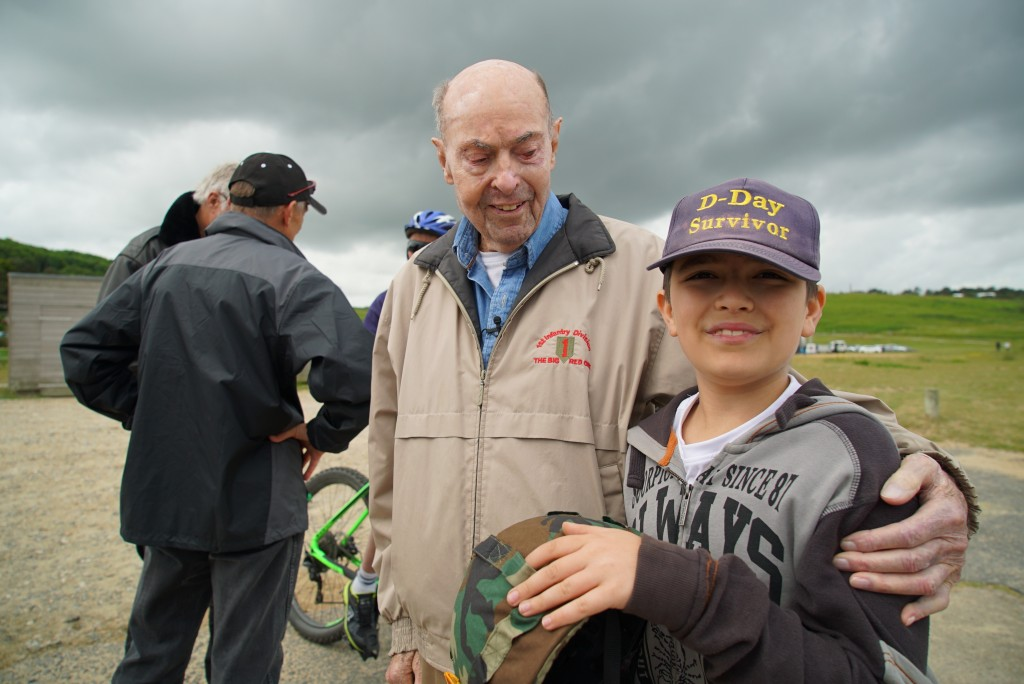 """D-Day veteran Ray Lambert shares his """"lucky hat"""" with a young Italian tourist at Omaha Beach in Colleville-sur-Mer, France, on Wednesday, June 5, 2019"""