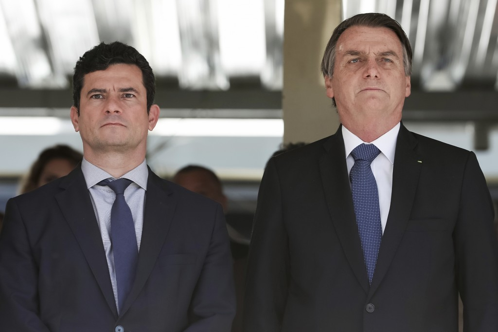 In this photo released by Brazil's Presidential Press Office, Brazil's President Jair Bolsonaro, right, and Justice Minister Sergio Moro attend a mili