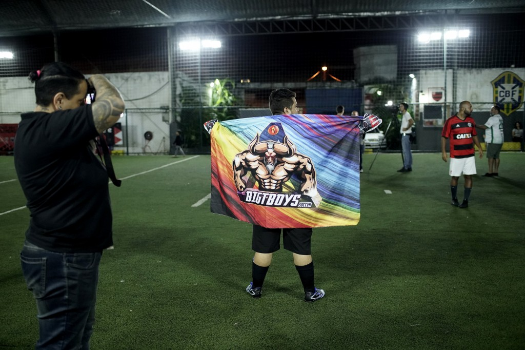 In this May 27, 2019 photo, Cristian Lins Silva, left, the founder of the Bigtboys transgender men's soccer team, takes a picture of the team's flag a