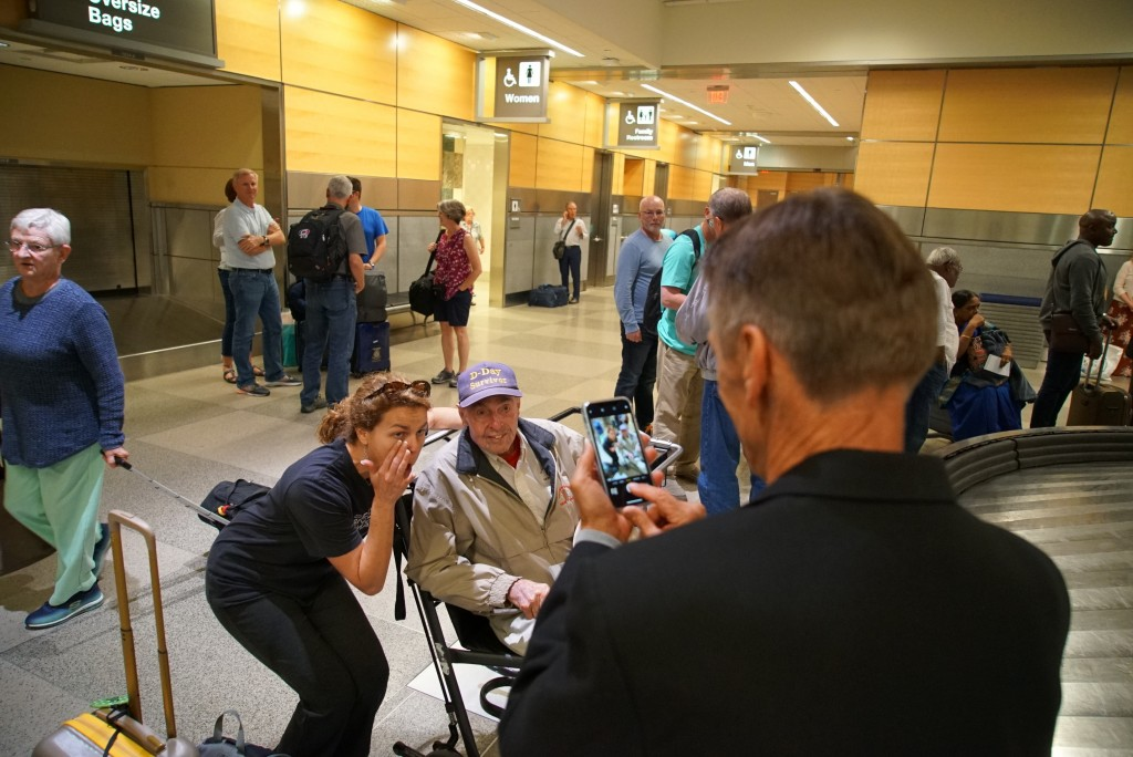Caroline Wright wipes away tears as she poses for a photo with D-Day survivor Ray Lambert in the baggage claim area at RDU International Airport in Mo