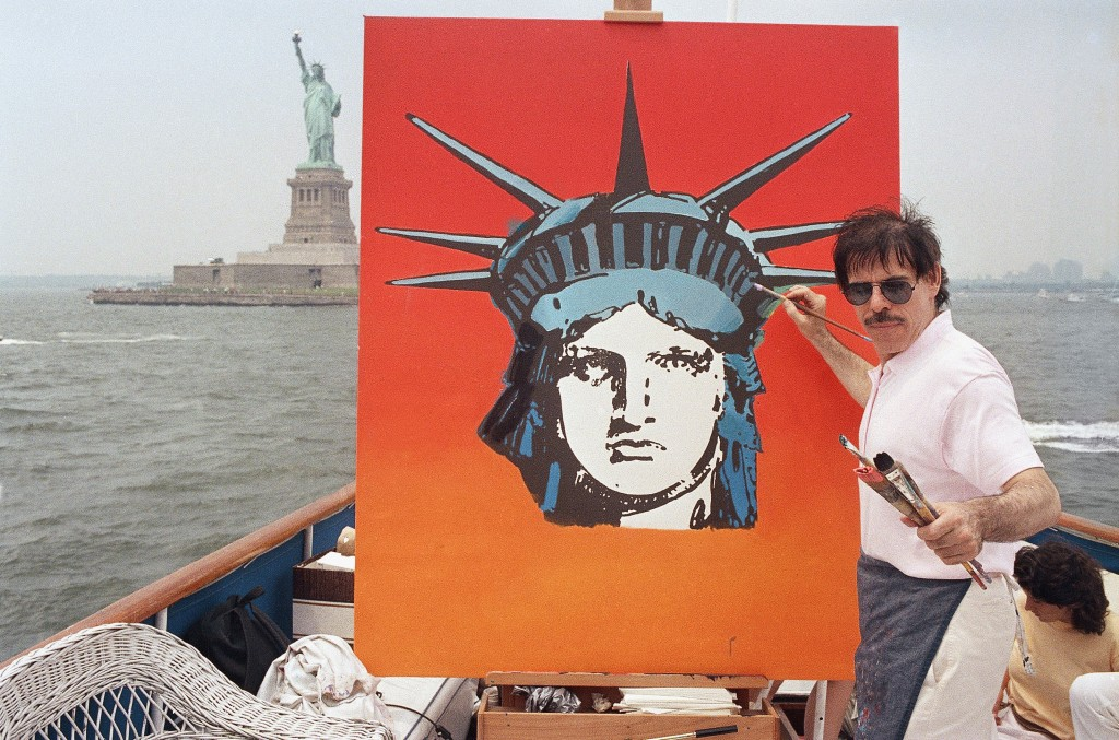 FILE - In this July 4, 1987, file photo, artist Peter Max works on a painting of the Statue of Liberty aboard a boat in New York Harbor, as part of th...