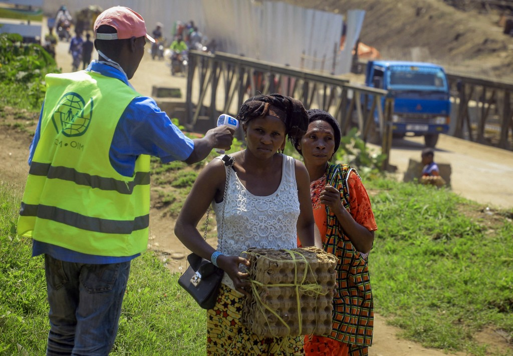 People crossing the border have their temperature taken to check for symptoms of Ebola, at the border crossing near Kasindi, eastern Congo Wednesday, ...