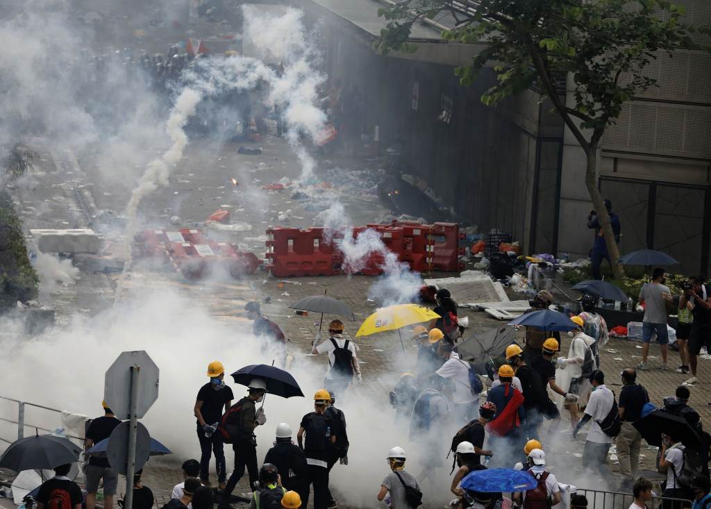 In this June 12, 2019, file photo, riot police fire tear gas toward protesters outside the Legislative Council in Hong Kong. (AP Photo/Vincent Yu)
