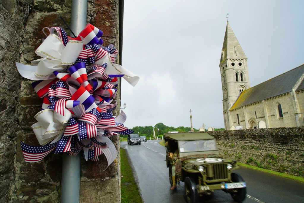 A vintage World War II jeep passes by a decoration along the main road in Colleville-sur-Mer, France, on Saturday, June 8, 2019. D-Day survivor Ray La