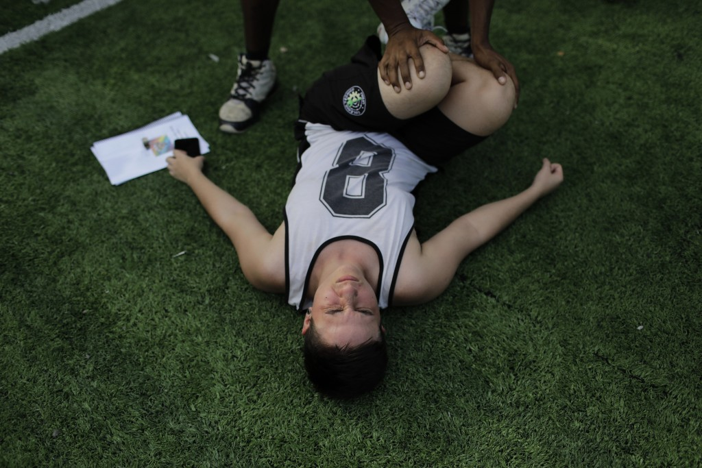 In this May 13, 2019 photo, Apollo Henrique stretches during a practice session with the Bigtboys, a transgender men's soccer team in Rio de Janeiro,