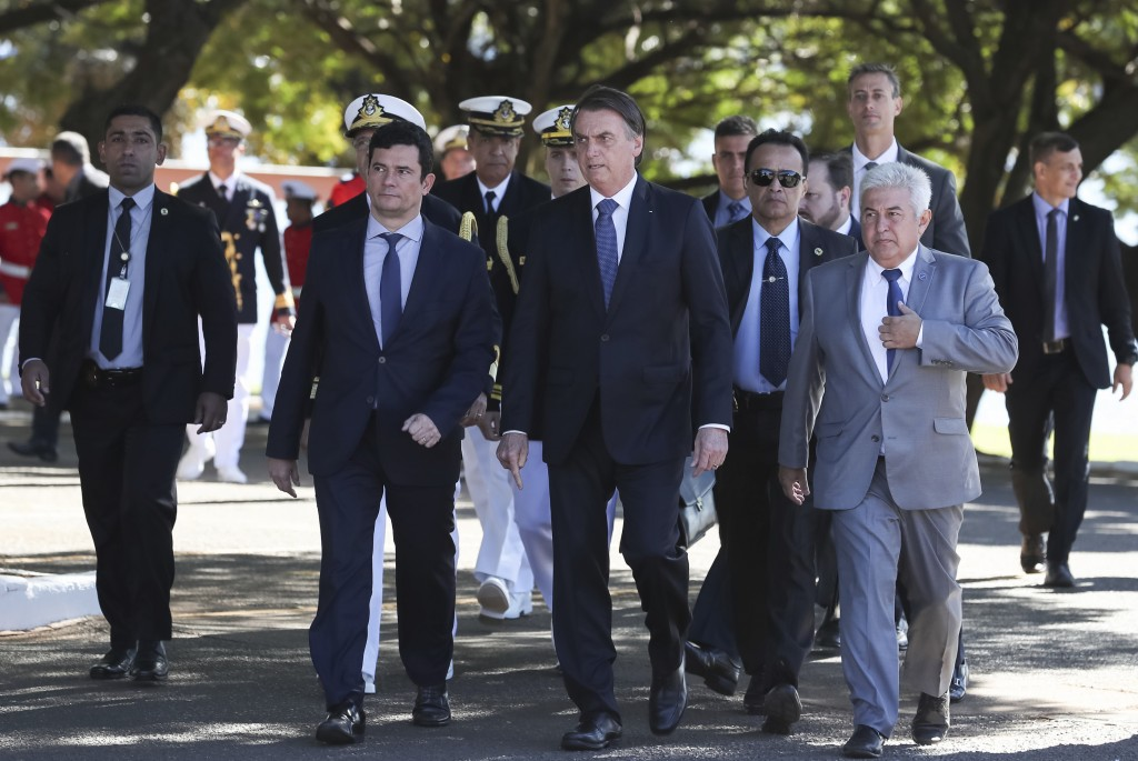 In this photo released by Brazil's Presidential Press Office, Brazil's President Jair Bolsonaro, second right, and Justice Minister Sergio Moro, secon...