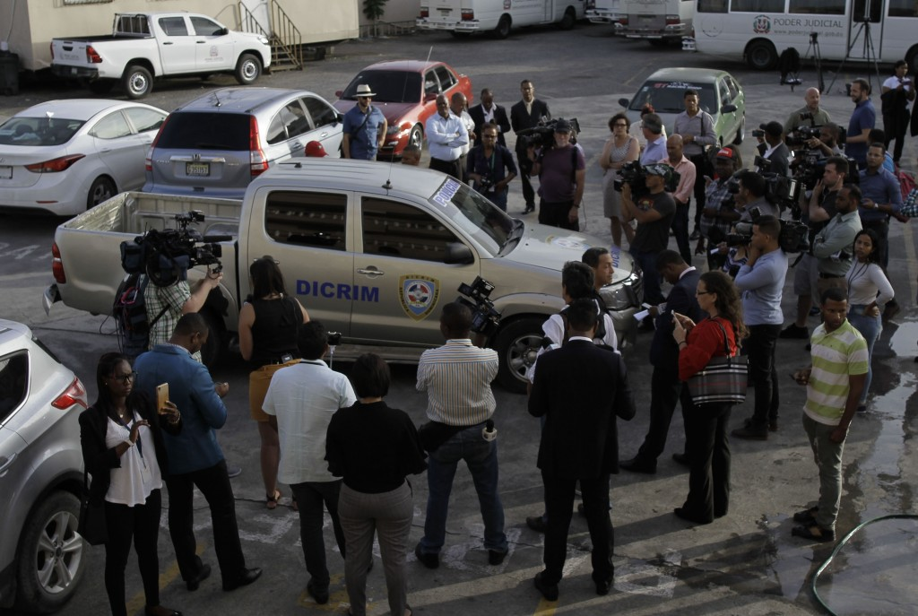 Journalists surround the police vehicle carrying Eddy Vladimir Féliz Garcia who was taken into custody in connection with the shooting of former Bosto...
