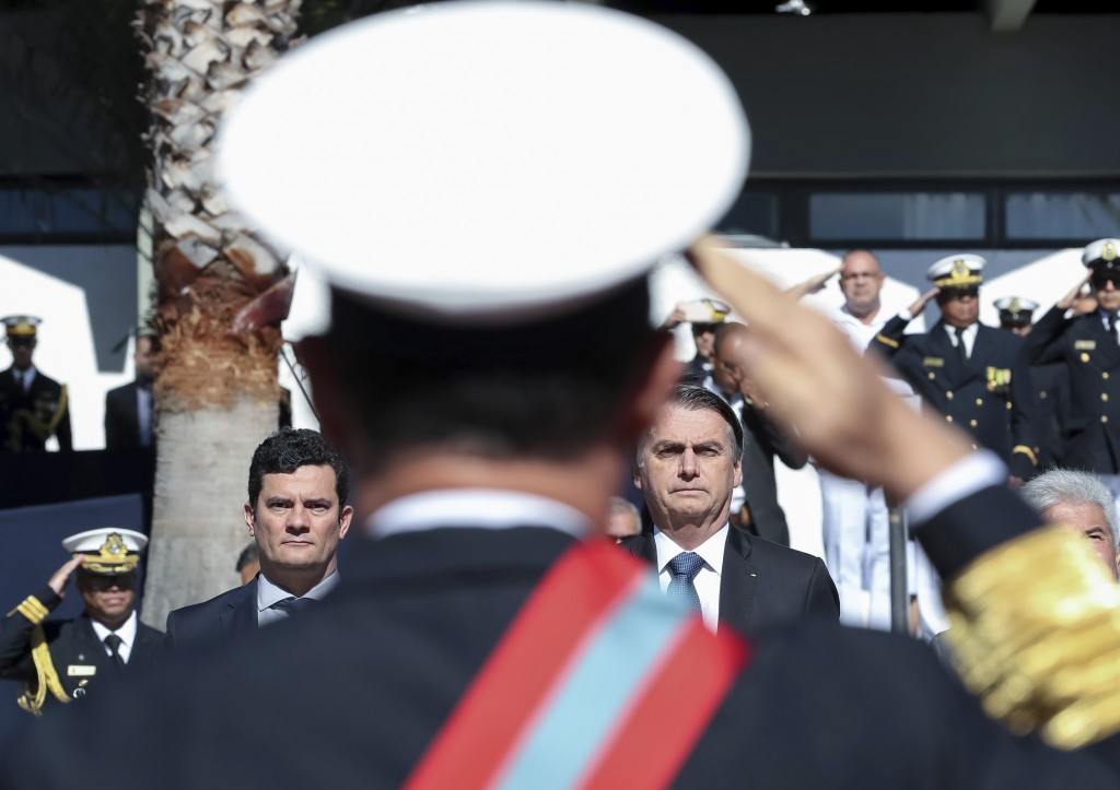 In this photo released by Brazil's Presidential Press Office, Brazil's President Jair Bolsonaro, right, and Justice Minister Sergio Moro attend a mili...