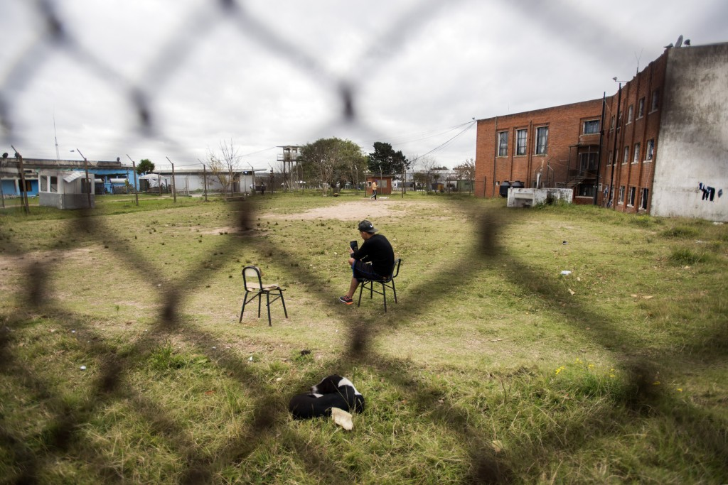 In this May 9, 2019 photo, an inmate uses his tablet to chat, at the Punta de Rieles prison in Montevideo, Uruguay. The prisoners enjoy significant fr...