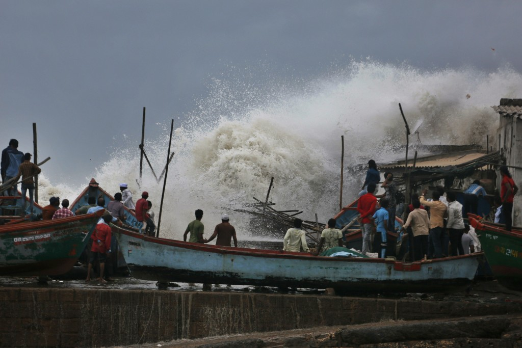 In this Wednesday, June 12, 2019, file photo, a waves crashes as people stand on boats on the Arabian Sea coast in Veraval, Gujarat, India. Indian aut