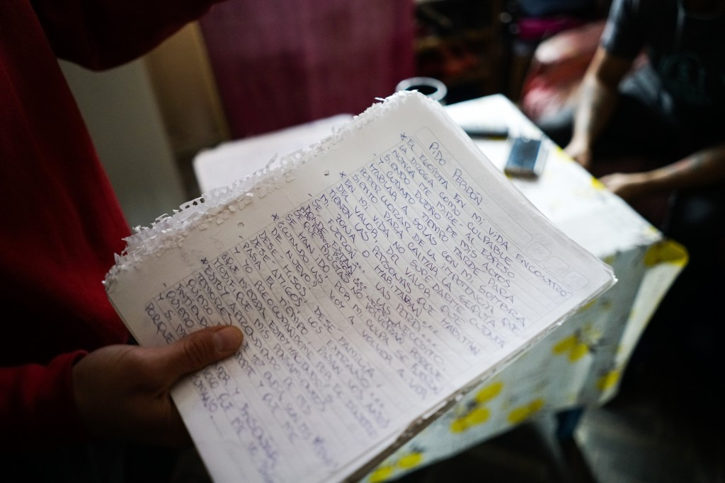 In this May 29, 2019 photo, inmate Federico Gonzalez, also known as Kung-Fu OmBijam, holds his handwritten lyrics inside his cell at the Punta de Riel...