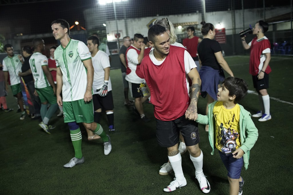 In this May 27, 2019 photo, Daniel de Farias Viana leaves the field with his girlfriend's son after playing a soccer game with his transgender men's t...