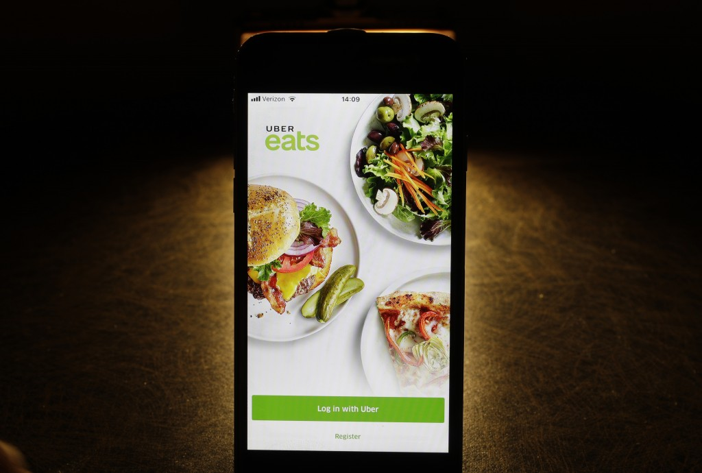 FILE - In this Feb. 20, 2018, file photo shows the Uber Eats app on an iPhone in Chicago.  Uber is testing restaurant food deliveries by drone. The co...