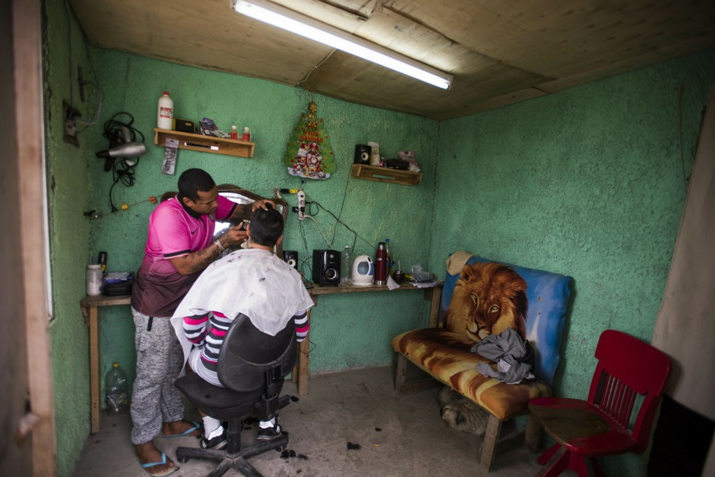 In this May 9, 2019 photo, an inmate at the Punta de Rieles prison that runs one of the existing barbershops, cuts the hair of another inmates t the p...