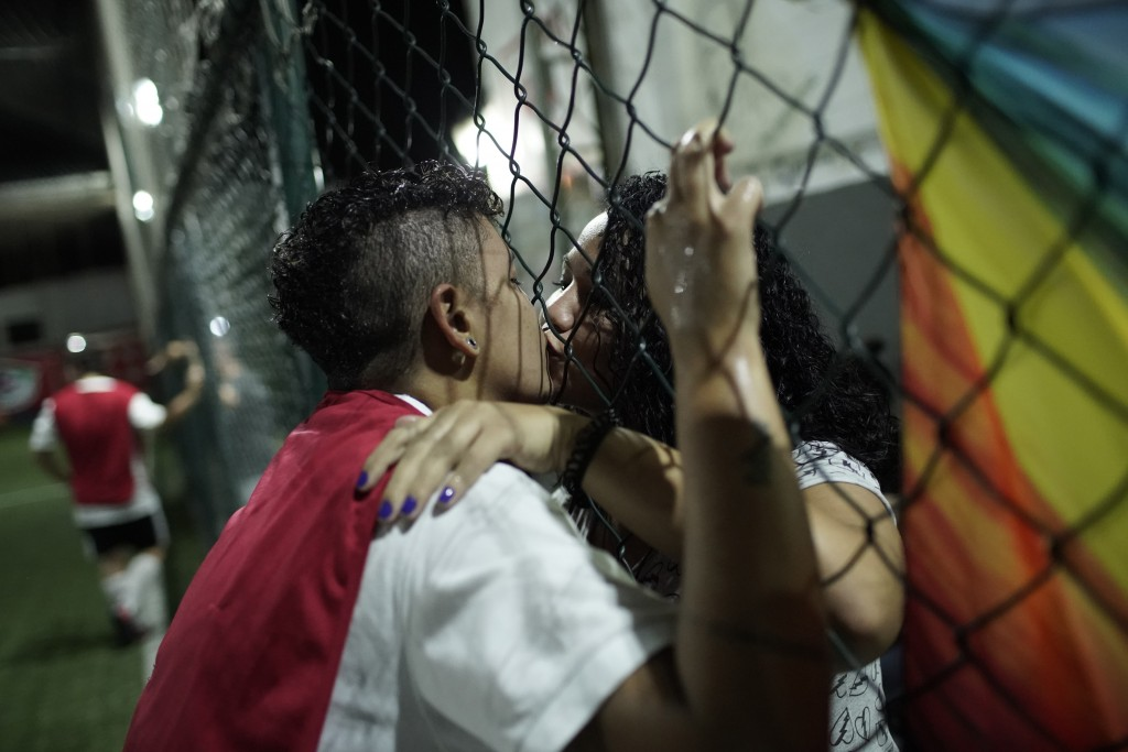 In this May 27, 2019 photo, Bernardo Pereira, 23, left, kisses his girlfriend on the sidelines of a game played by the Bigtboys transgender men's socc...