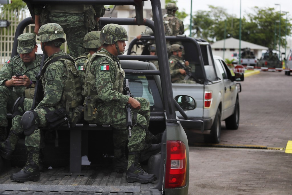 Mexican soldiers ride in the back of a pick up truck as they escort the caravan carrying Mexico's Minister of Defense in Tapachula Mexico Tuesday