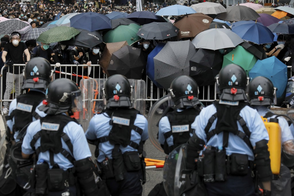 In this June 12, 2019, file photo, policemen line a perimeter as they watch protesters use umbrellas to shield themselves near the Legislative Council...