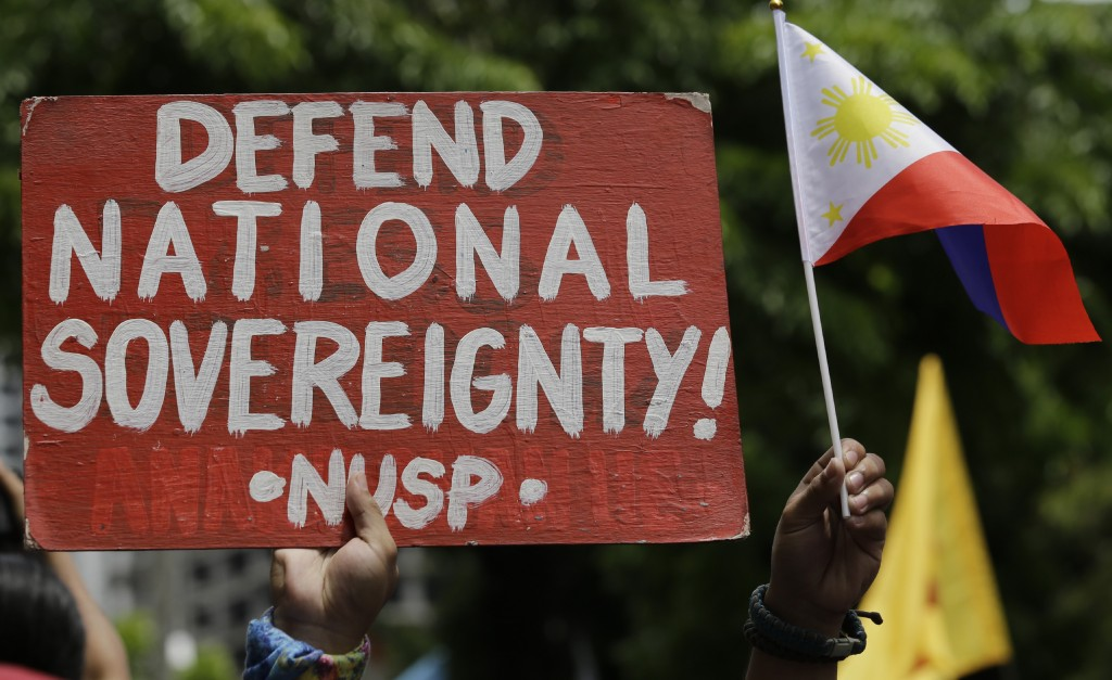 A protester holds a slogan during a rally outside the Chinese Consulate in the financial district of Makati, metropolitan Manila, Philippines to mark