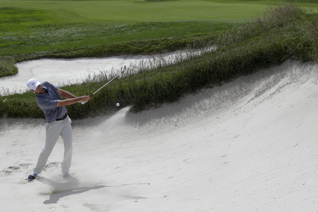 Brooks Koepka hits out of the bunker on the first hole during a practice round for the U.S. Open Championship golf tournament Tuesday, June 11, 2019, ...