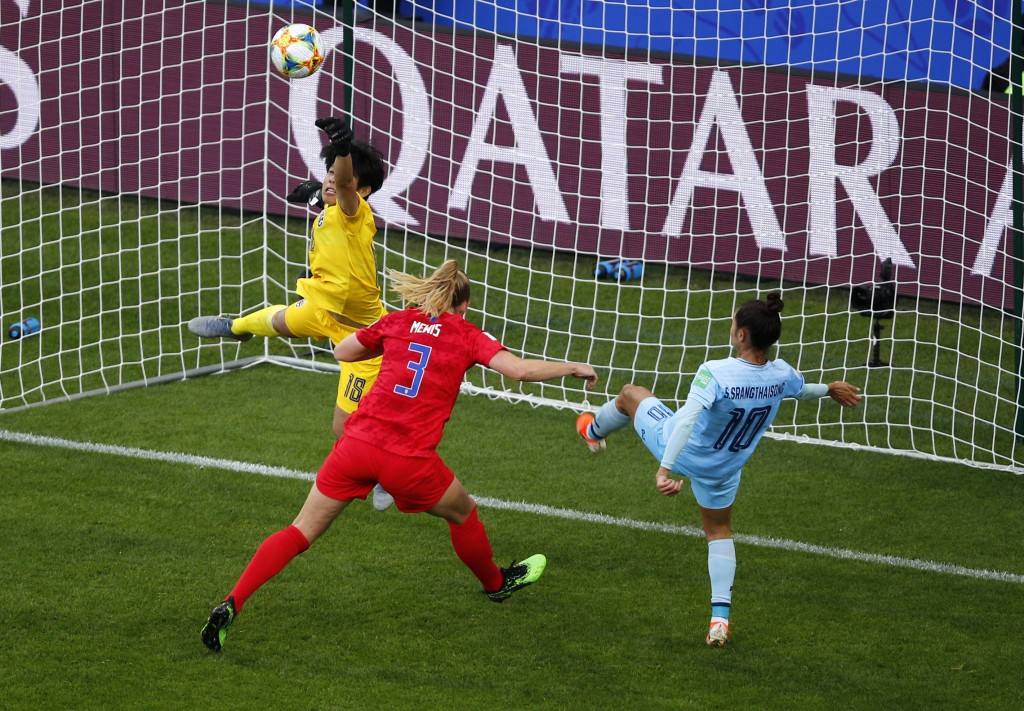 Thailand goalkeeper Waraporn Boonsing, left, punches the ball clear of United States' Samantha Mewis and teammate Sunisa Srangthaisong during the Wome
