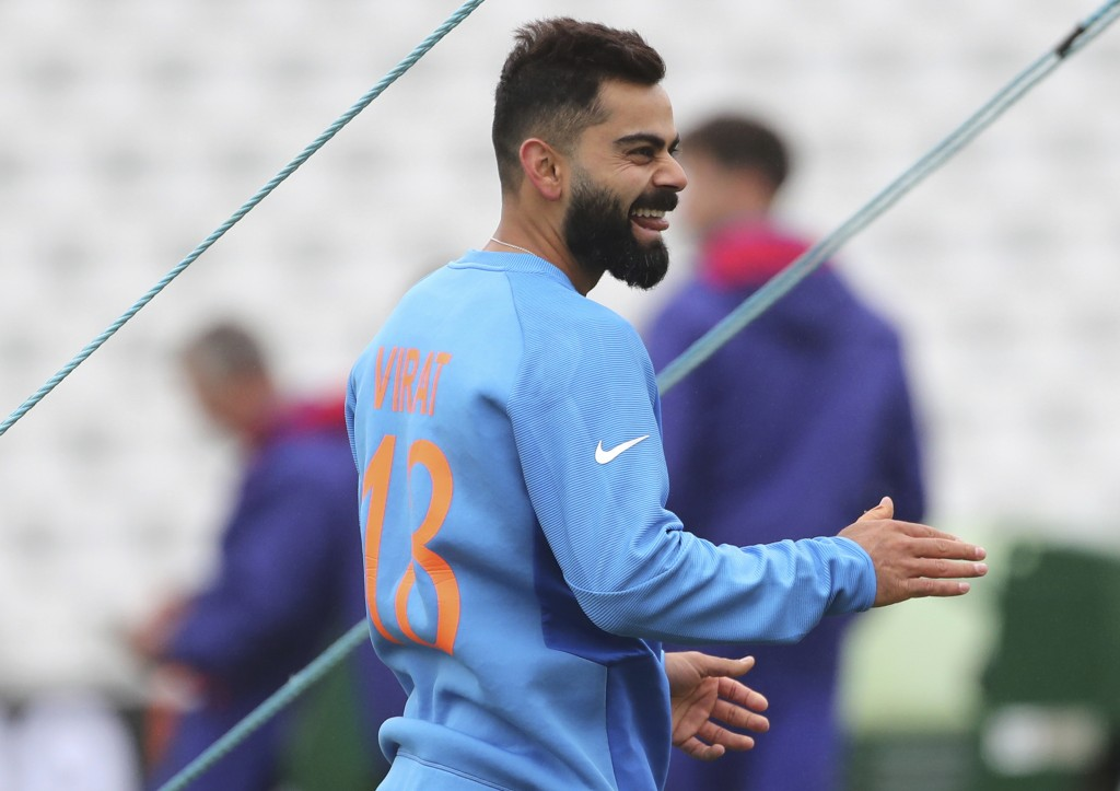 India's captain Virat Kohli laughs during a training session ahead of their Cricket World Cup match against New Zealand at Trent Bridge in Nottingham,...