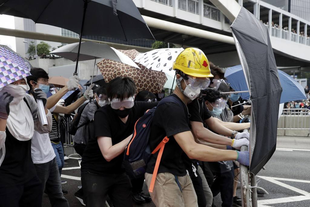 In this June 12, 2019, file photo, protesters wear protection gears and use umbrellas to shield themselves as they gather near the Legislative Council