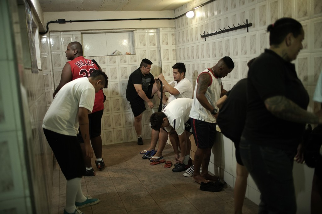 In this May 27, 2019 photo, soccer players from the Bigtboys transgender men's soccer team get ready in their locker room in Rio de Janeiro, Brazil. B