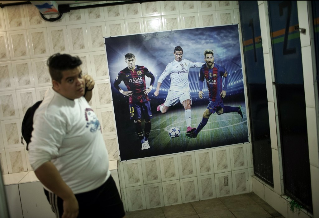 In this May 27, 2019, a player with the transgender men's Bigtboys soccer team walks past a poster of soccer stars Neymar, Ronaldo, and Messi, inside ...