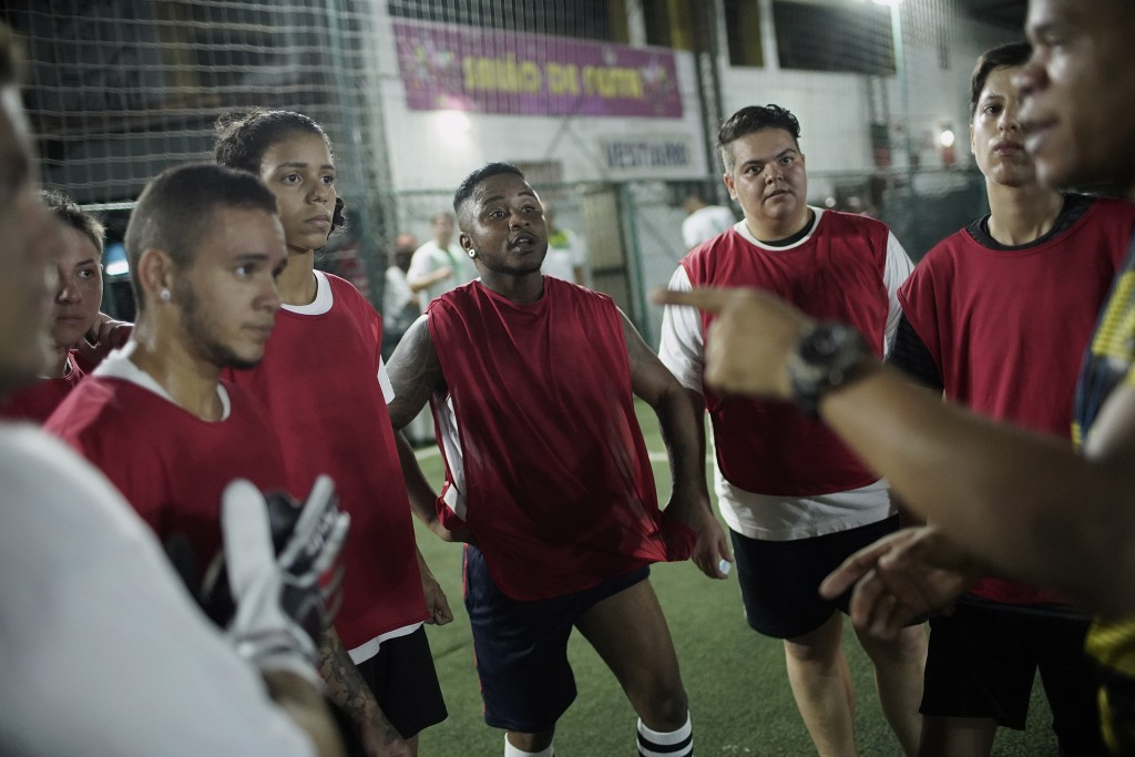 In this May 27, 2019 photo, Bigtboys transgender men's soccer player Bruno dos Santos, center, and his teammates listen to their coach during a game a...