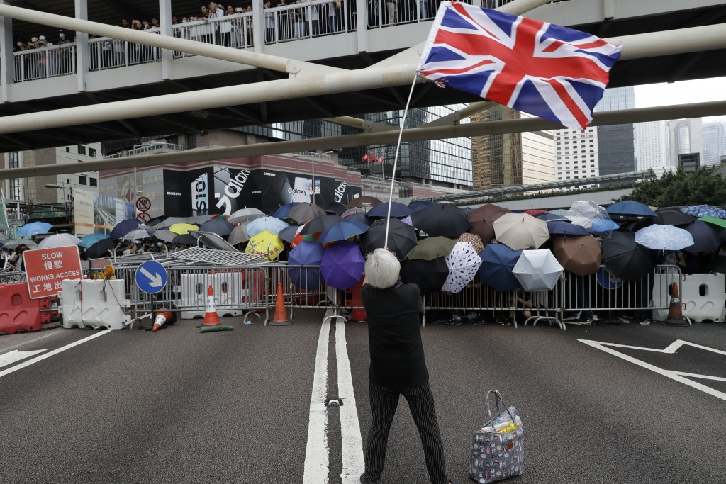 In this June 12, 2019, file photo, a protester waving the Union Jack joins other protesters using umbrellas to shield themselves outside the Legislati...