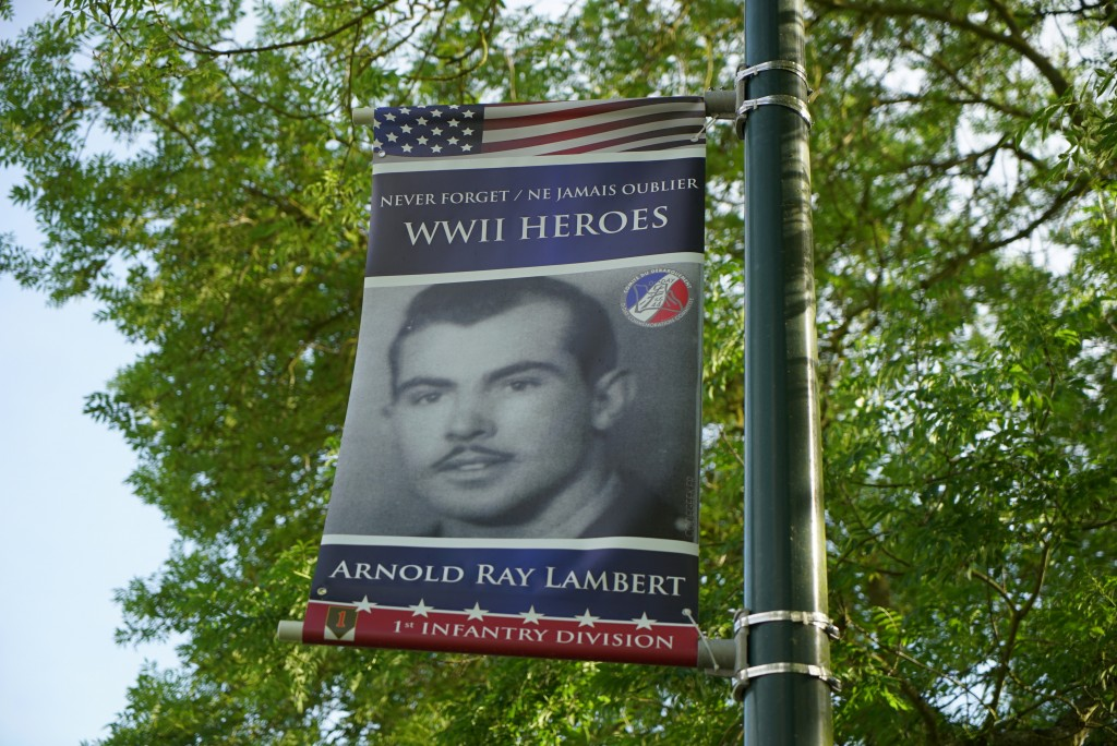 A banner honoring D-Day survivor Ray Lambert hangs on a post near the entrance to the American Military Cemetery in Colleville-sur-Mer, France, on Wed