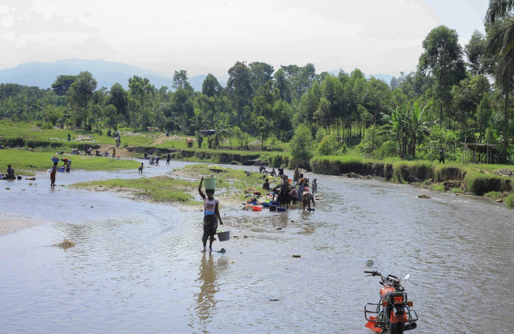 Local residents wash clothes and wade in the shallow Lubiriha River, an area that is popular with those who want to cross into Uganda without passing